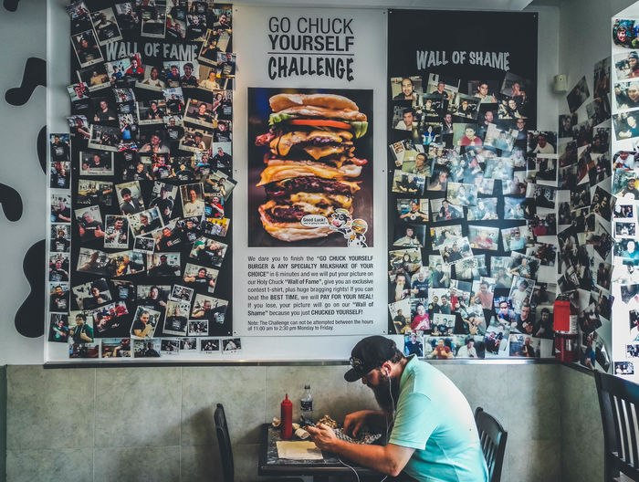 Have lunch in front of the Wall of Fame/Shame Adult Adults Only Burger Time Burgerlover Communication Day Indoors  Lunchtime Only Men People Restaurant Streetphotography Toronto Wall Of Fame Wall Of Shame The Street Photographer - 2017 EyeEm Awards