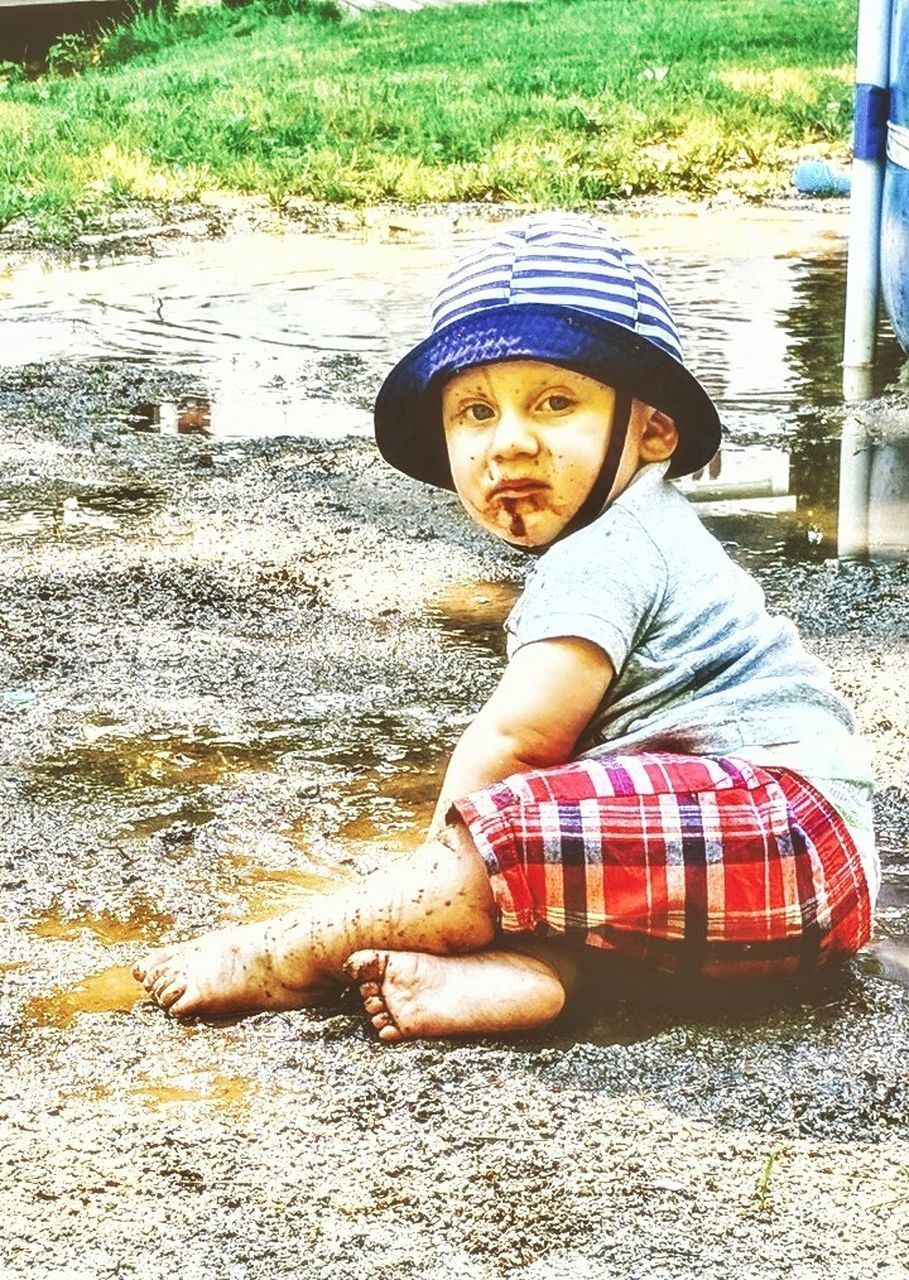real people, boys, childhood, elementary age, one person, full length, sitting, outdoors, day, leisure activity, lifestyles, cap, looking at camera, portrait, grass, water
