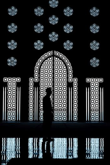Silhouette man standing against window with reflection on floor at mosque hassan ii