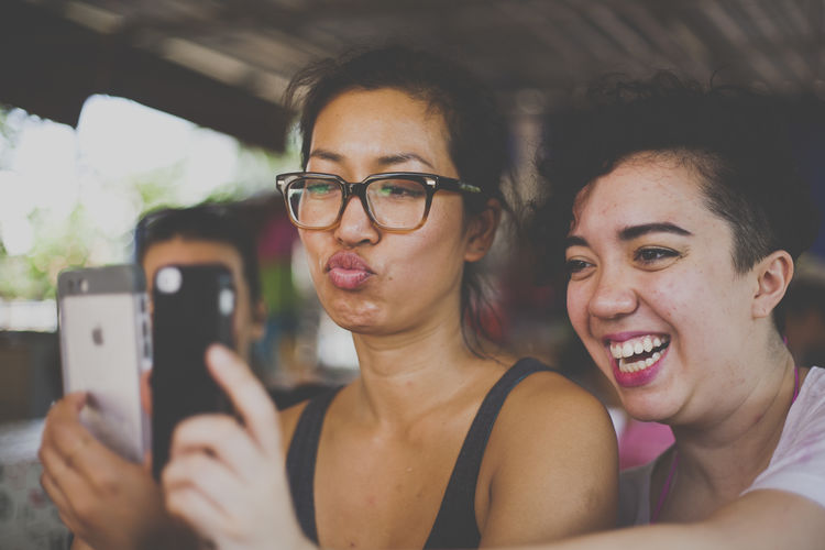 Focus On Foreground Friends Front View Headshot IPhone Leisure Activity Lifestyles Person Silly Face Smart Phone Young Adult Young Men