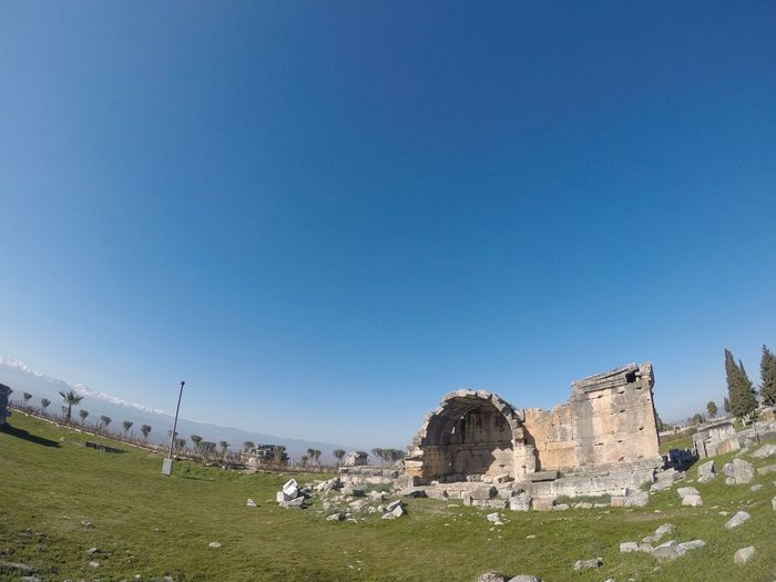 Old ruins on field against clear blue sky