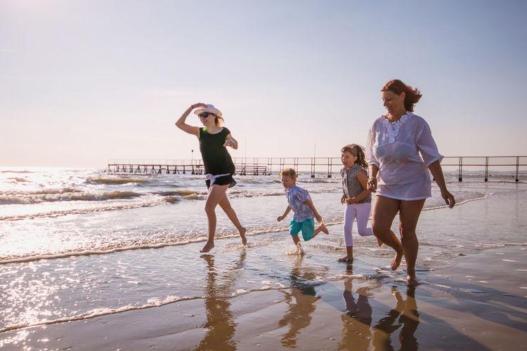 Full Length Family Running At Beach Against Sky