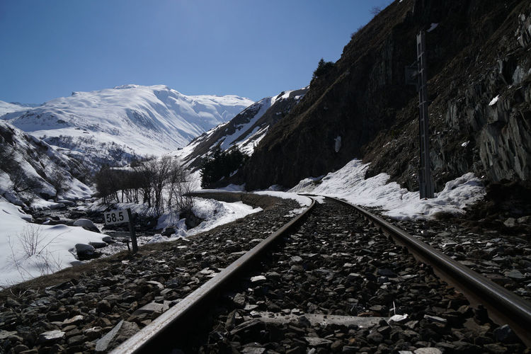 Railroad tracks amidst snowcapped mountains against clear sky