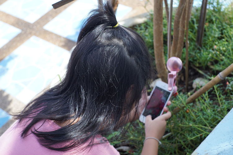 Rear view of girl using phone