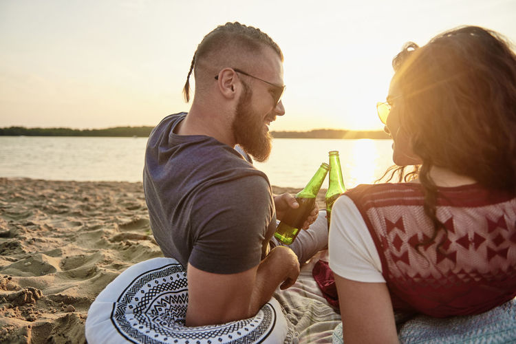 Smiling couple with beer bottles sitting at beach against sky during sunset