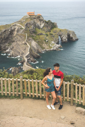 Full length of couple standing by railing against sea