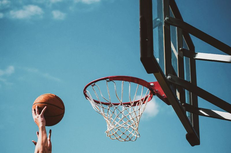Cropped hands aiming basketball into hoop against sky