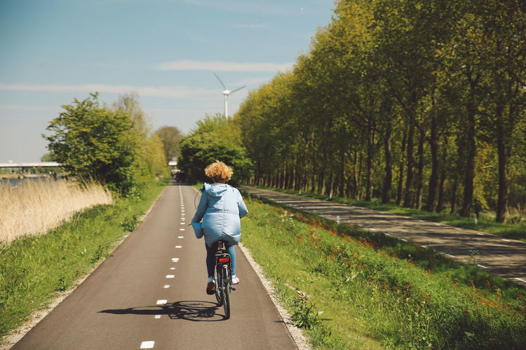 Rear View Of Woman Riding Bicycle On Road During Sunny Day