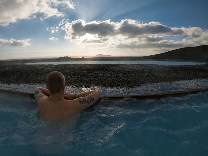 Man relaxing in swimming pool against sea