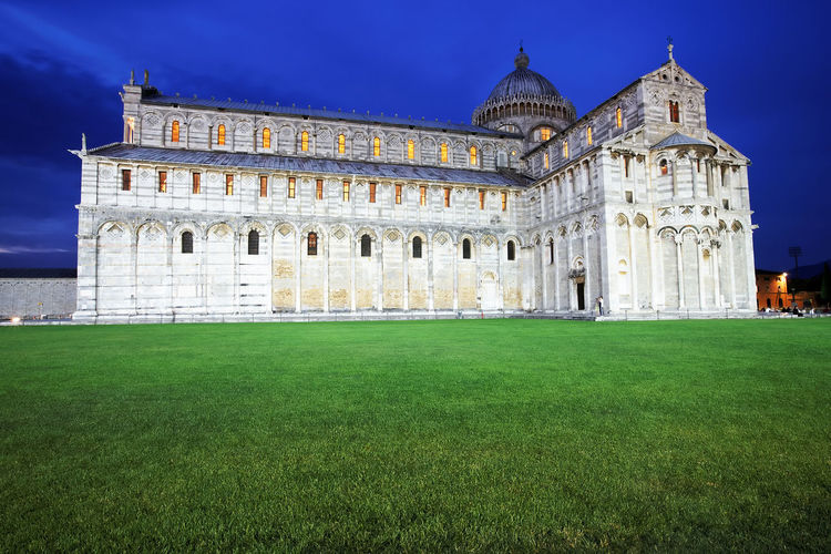 Pisa cathedral by lawn against blue sky at dusk