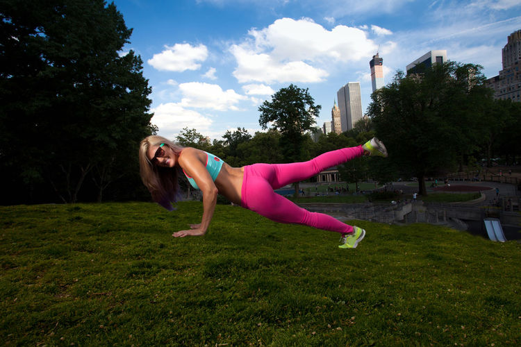 Portrait of smiling beautiful woman doing push-ups on grassy field at park
