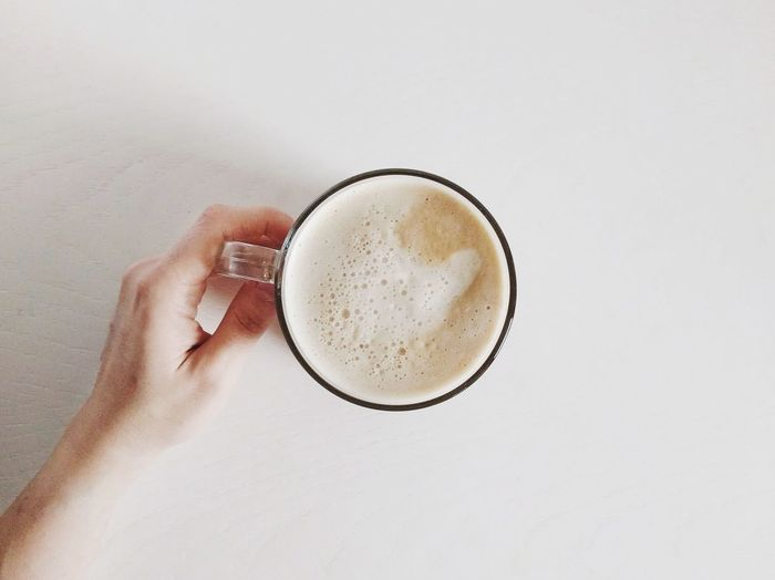 Coffee first. Breakfast White Background Cappuccino Hot Drink Ready To Drink Human Body Part Drink Human Hand Coffee - Drink Food And Drink Frothy Drink Refreshment Latte Indoors  Directly Above Holding Coffee Cup One Person