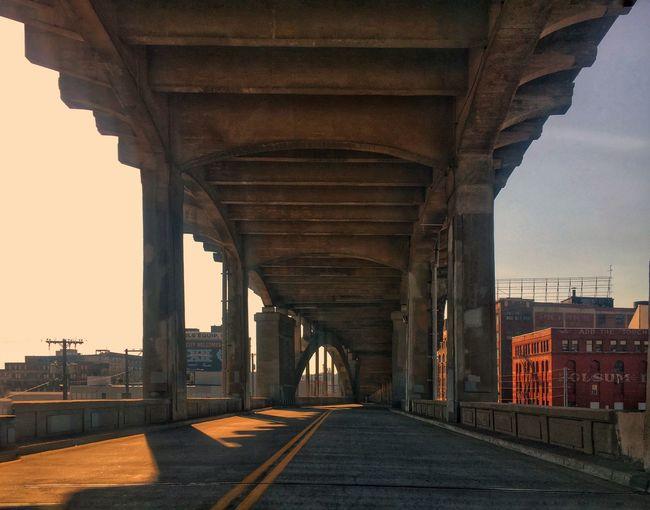 Walkway under bridge in city against sky