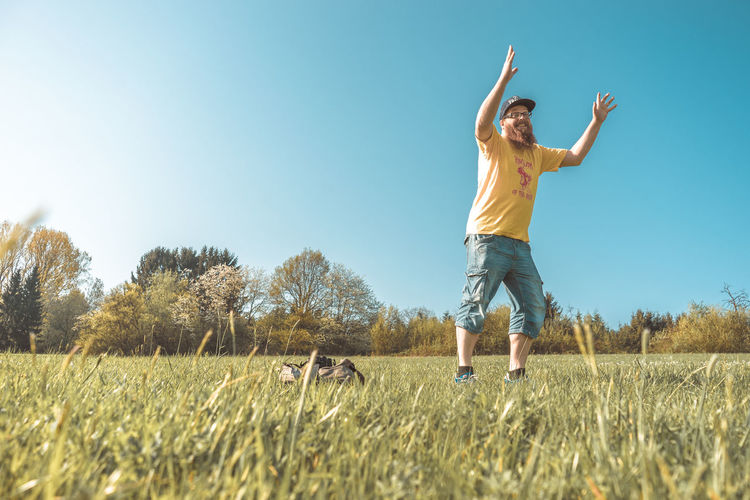 Arms Raised Casual Clothing Clear Sky Day Field Freedom Full Length Fun Grass Human Arm Land Landscape Leisure Activity Lifestyles Limb Nature One Person Outdoors Plant Real People Sky Springtime Sunlight Yellow