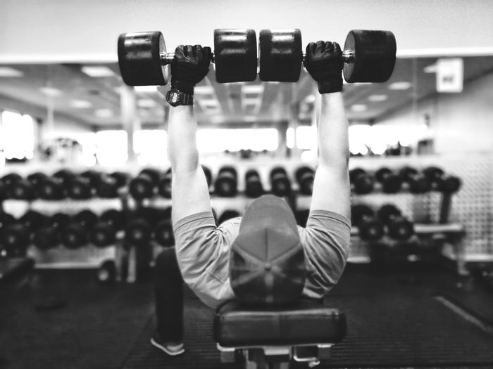 Man Lifting Dumbbells While Exercising In Gym