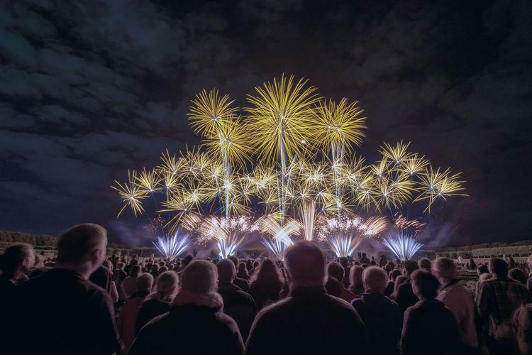 People looking at firework display at night