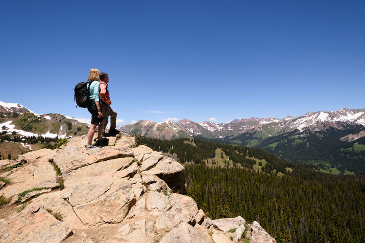 Man and woman standing on rock against mountains and blue sky