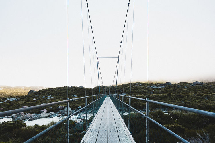Symmetrical suspension bridge against foggy sky. hooker valley track, mount cook national park