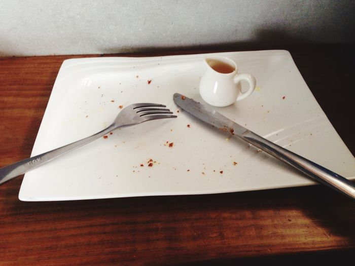 Close-Up Of Leftovers With Cutlery And Coffee In Tray On Table