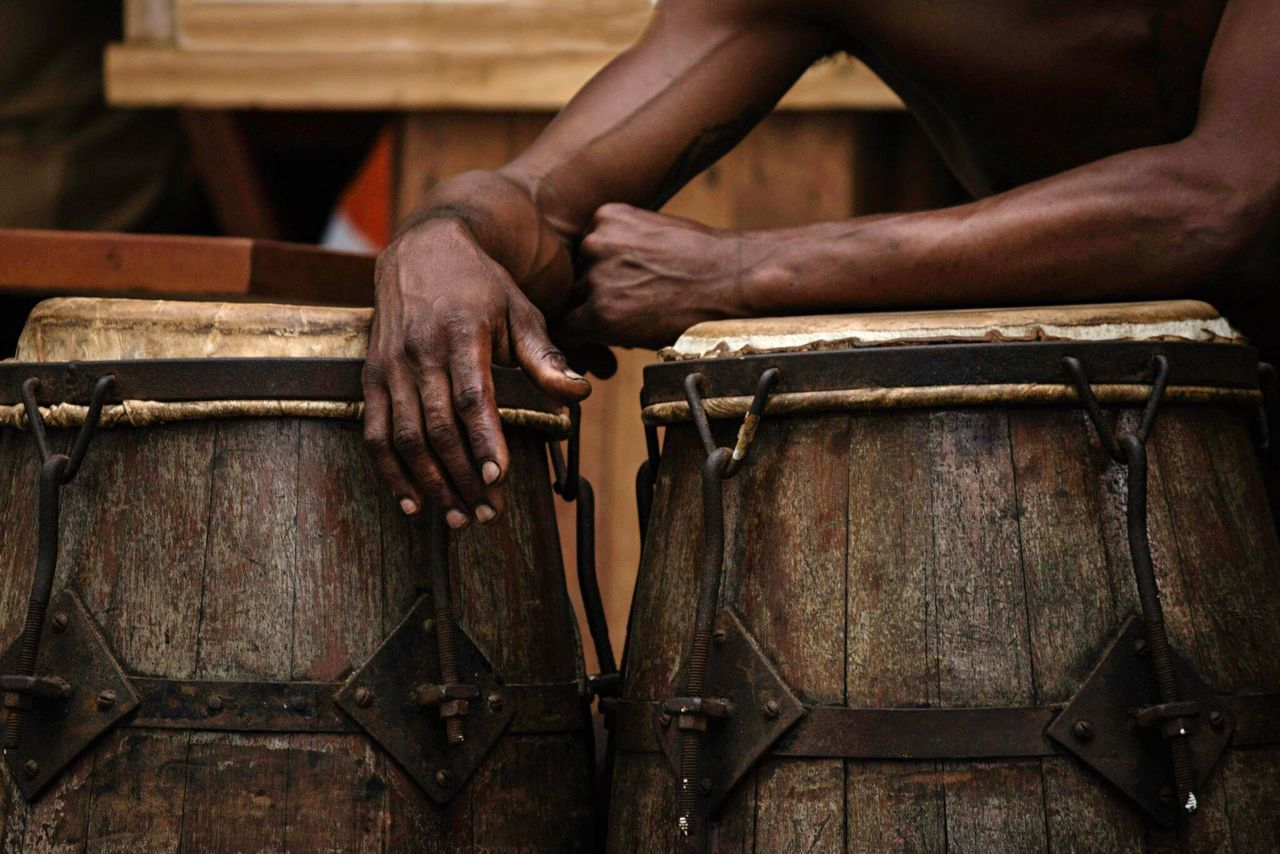 Midsection of man leaning on drum