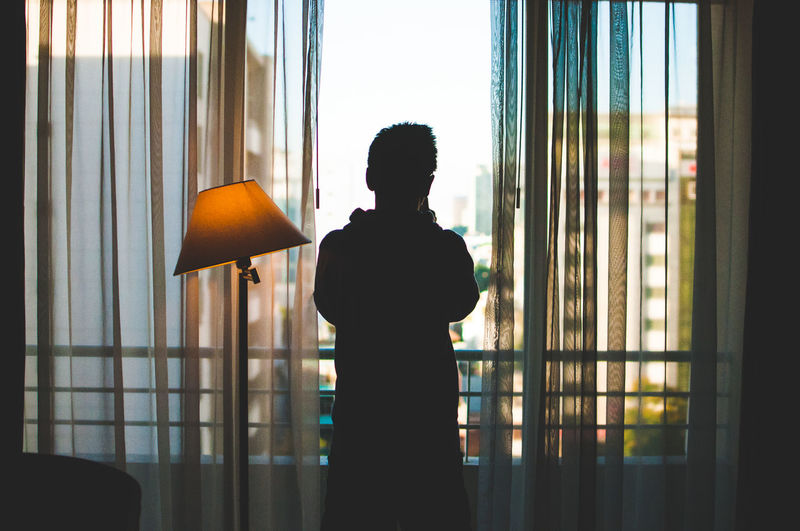 Rear view of man standing while looking through window at home