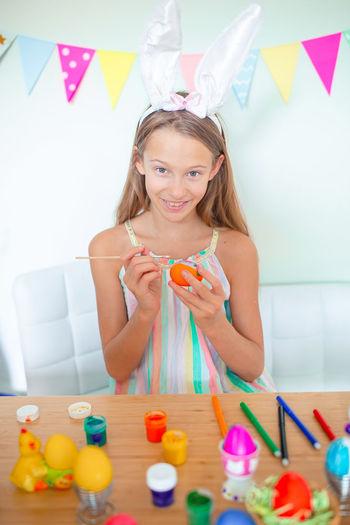 Portrait of girl painting egg