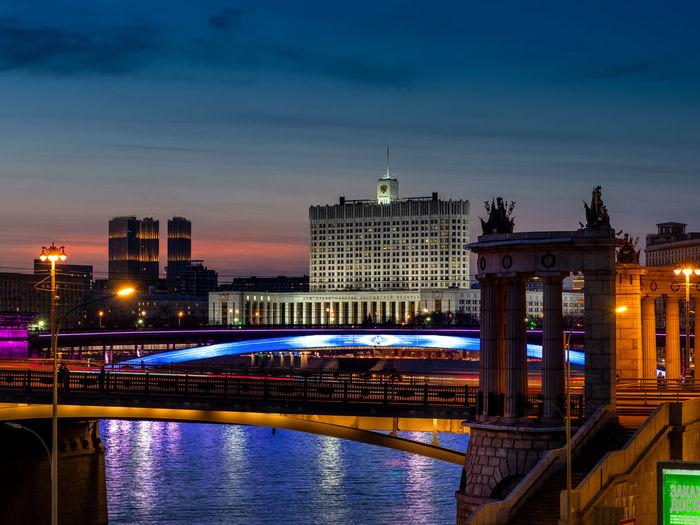 Illuminated bridge over river against buildings at dusk