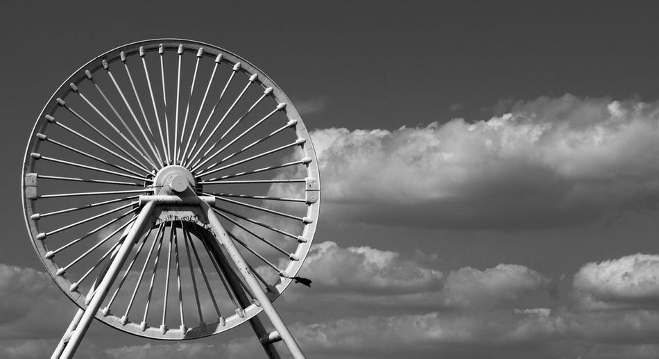 Low angle view of pit wheel against sky