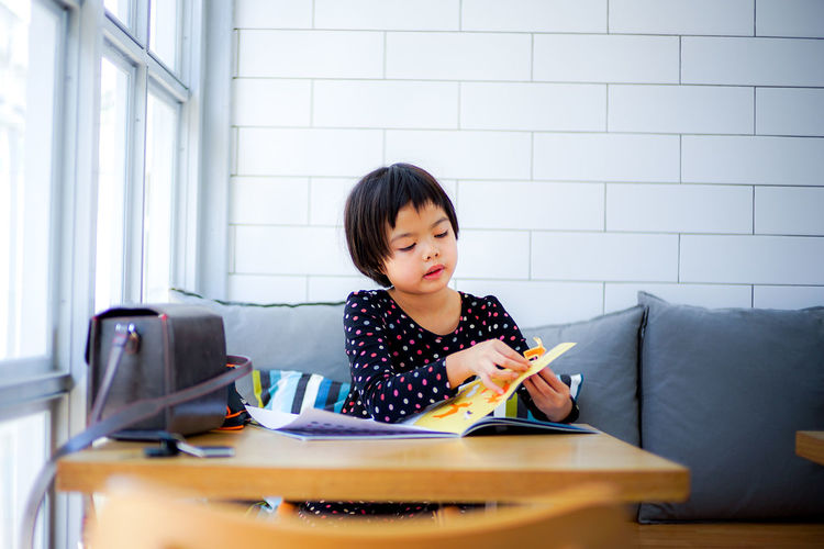 Cute girl reading book while sitting on sofa at home