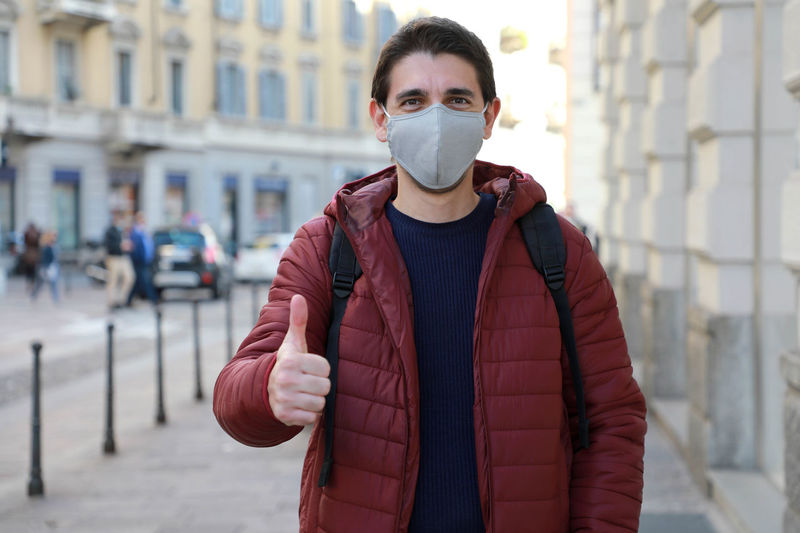 Portrait of man wearing mask gesturing while standing on footpath