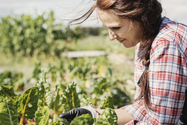 Side view of young woman looking at plants