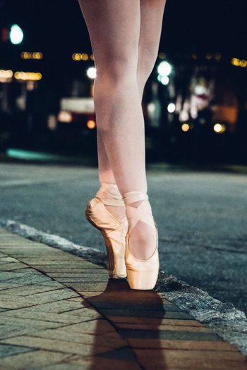Low section of ballet dancer dancing on street at night