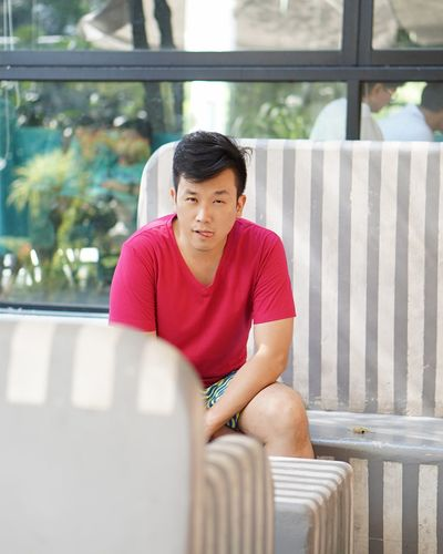 Portrait of mid adult man sticking out tongue while sitting on bench