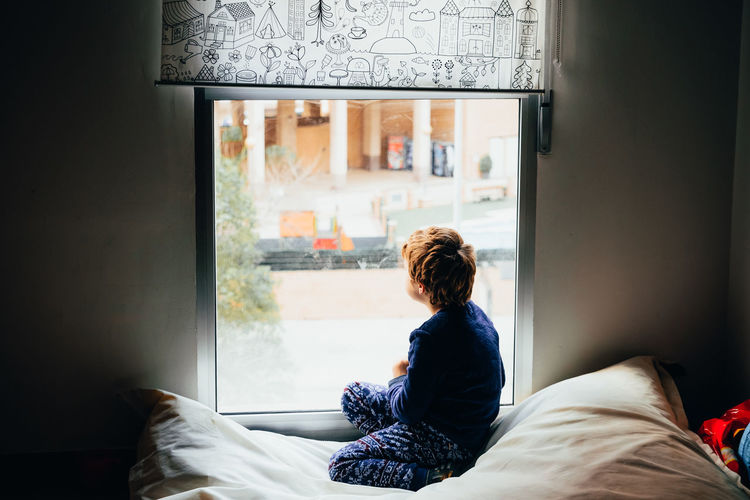 Full length of boy looking through window while sitting on bed at home