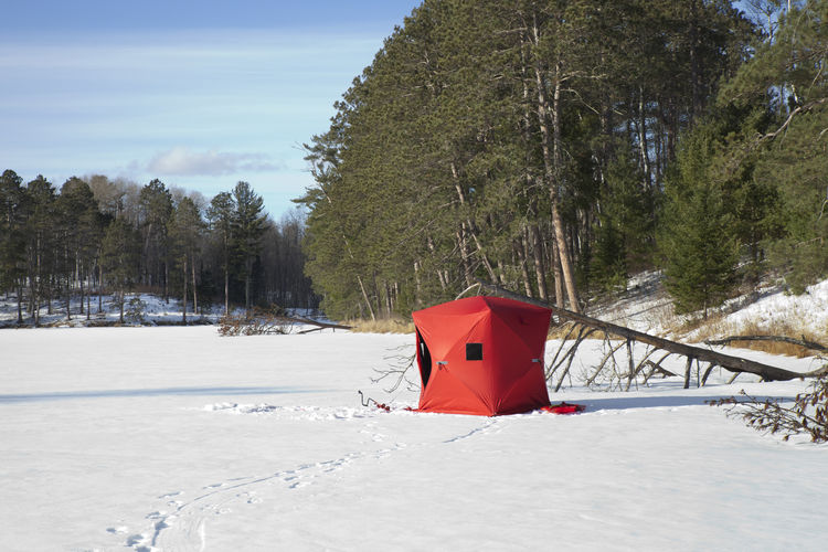 A red portable ice fishing shelter on a remote frozen lake in Minnesota Afternoon Frozen Ice Ice Fishing Minnesota Red Sunlight USA Auger Blue Fishing Lake Landscape Pine Tree Portable Remote Shelter Sky Snow Tracks In Snow White Wilderness