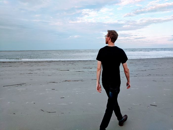 Full length rear view of man standing on beach