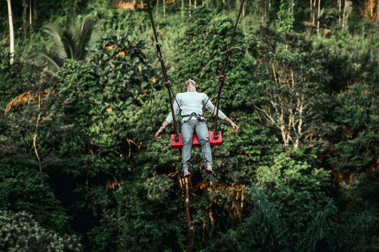 Man standing by plants in forest
