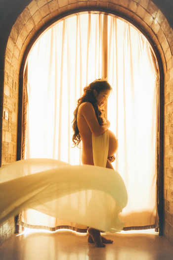 Side View Of Naked Pregnant Woman Standing By Window At Home