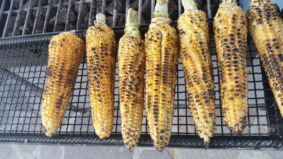 High Angle View Of Roasted Corns On Metal Grate Over Burning Charcoal