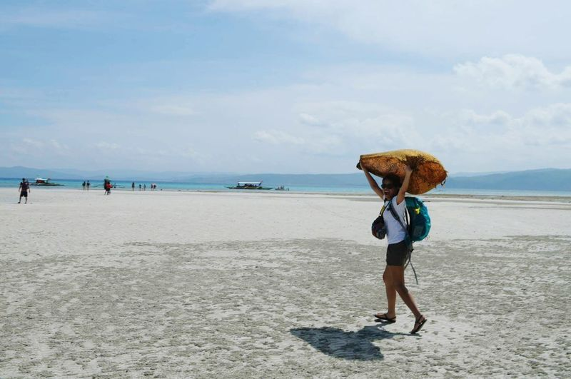 Full length of happy traveler carrying sack on head while walking on beach