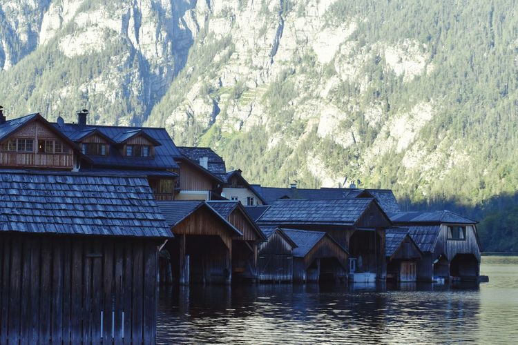 Houses by lake and buildings against mountain