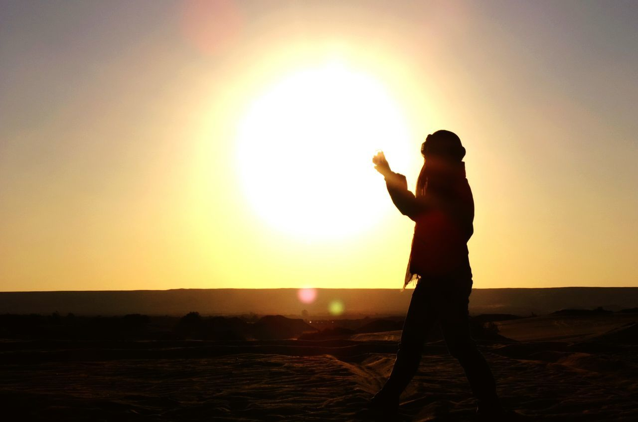 Side View Of Person Walking On Field At Sunset
