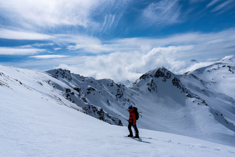 Full length of person skiing on snowcapped mountain against sky