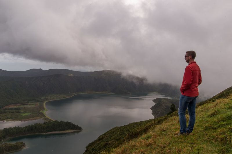 Side view of man standing on mountain by lake against cloudy sky