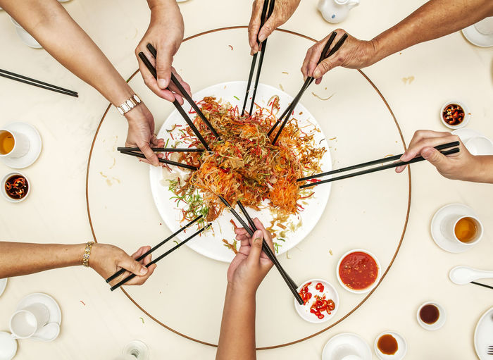 Top view of hands using chopsticks ready to toss into the air the mixture of shredded vegetables, ingredients and salmon. Yee Sang is often served during Chinese New Year. Chinese Food Condiments  Cuisine Hands Chinese New Year Directly Above East Asian Food Gourmet High Angle View Holding Indoors  Oriental People Table Top View Using Chopsticks Yee Sang Yusheng Visual Creativity
