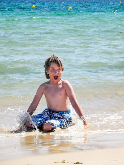 Beach Boys Cheerful Child Childhood Children Only Fun Happiness Mouth Open One Boy Only One Person Outdoors Playing Portrait Screaming Sea Shirtless Shouting Splashing Summer Swimming Water Wet