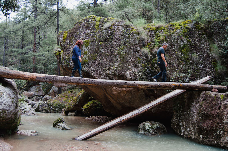 People standing on rock by river in forest