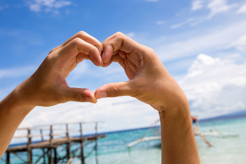 Close-Up Of Hands Making Heart Shape Against Sea