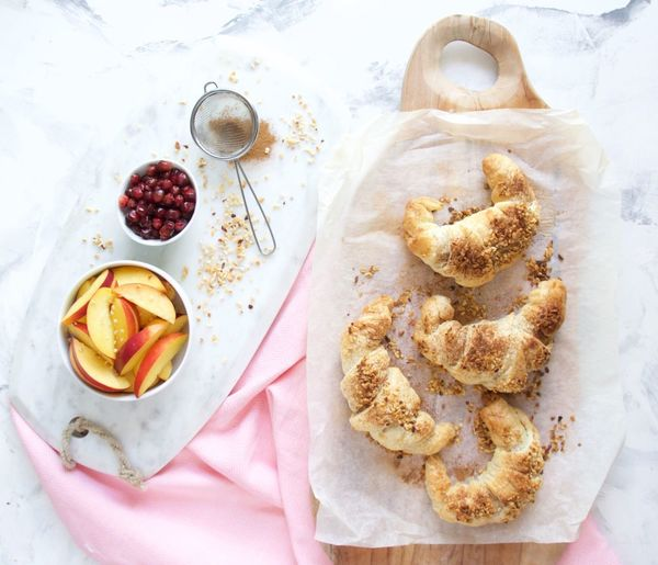 High angle view of croissant and fruits on table