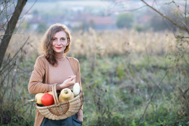 Portrait of smiling woman holding fruits in basket standing against field